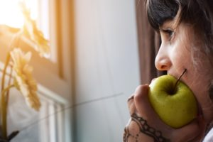 Kid eating green apple