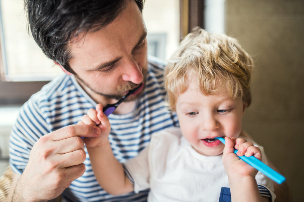 Father brushing his teeth with a toddler